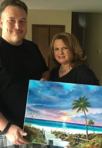 1 - Testimonial -Art_-_Christy_Krueger_&_Donovan_Campbell_Holding_A_Painting